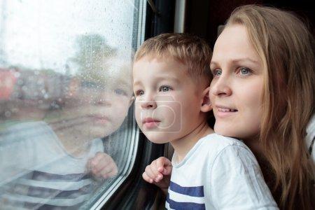 Madre e hijo mirando a través de una ventana de tren