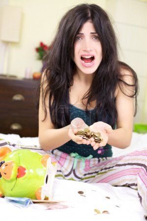 Photo for Beautiful woman with no job counting the money she has left in piggy bank shouting - Royalty Free Image