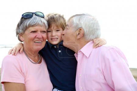 Happy kid getting kissed by grandpa and hugged by grandmother