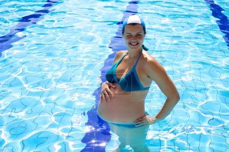 Gorgeous pregnant woman in swimming pool winking eye