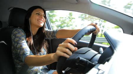Happy woman talking on the phone while driving car