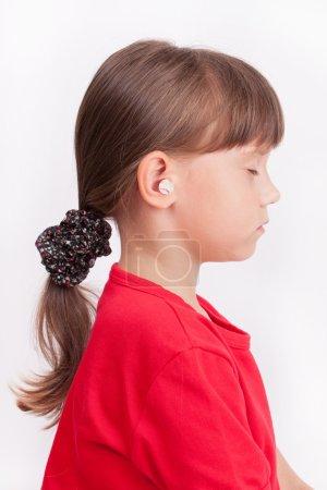Photo pour Petite fille mignonne avec oreille bouchons dans les oreilles - image libre de droit