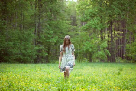 Photo for Young woman walking on a forest glade - Royalty Free Image