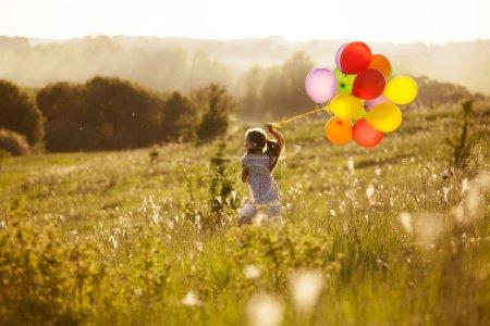 Photo pour Fille en cours d'exécution sur le champ de pissenlits avec ballons gonflables - image libre de droit