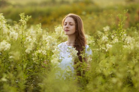 Photo for Happy young woman with eyes closed among the wildflowers - Royalty Free Image