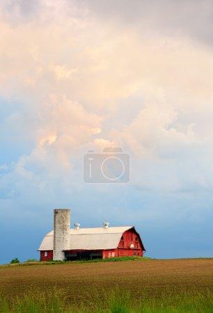 Photo pour Un ciel de coucher de soleil spectaculaire plane sur une grange rouge avec silo et panier de basket dans le Midwest des États-Unis . - image libre de droit