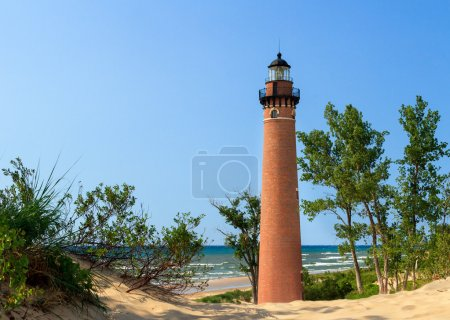 Photo for The natural red brick lighthouse  at Michigan's Little Sable Point is viewed through sand dunes overlooking Lake Michigan surf. - Royalty Free Image