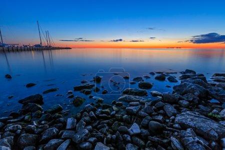 Photo pour Leuchtenden Sonnenuntergang Himmel leuchtet die Marina im Schwesterhotel Bay, Door County, wisconsin. - image libre de droit