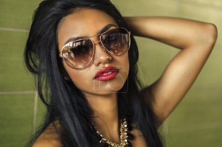 Beautiful young woman wearing sunglasses...