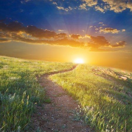 Photo pour Route parmi les collines au coucher du soleil - image libre de droit