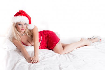 Photo for Gorgeous Sexy Woman In Santa Hat curled up on a bed - Royalty Free Image