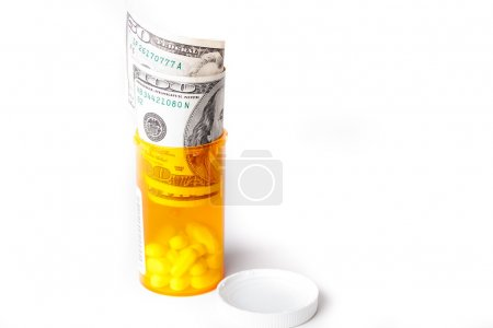 Prescription Drugs in a container with a hunderd dollar bill
