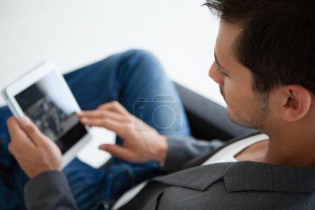 Photo pour Gros plan image recadrée d'un homme d'affaires attrayant dans la vingtaine travaillant sur un mini think pad - image libre de droit