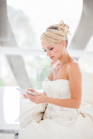 Smiling beautiful blond bride sitting at a table with a Mini tou