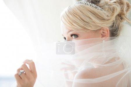 Photo pour Magnifique mariée blonde souriante devant une fenêtre de l'appartement à un hôtel moderne, un pic au cours de son voile - image libre de droit