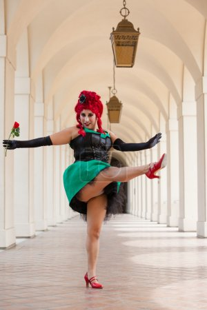 Photo for Pretty Woman with a rose dancing wearing a period piece bright Red wig - Royalty Free Image
