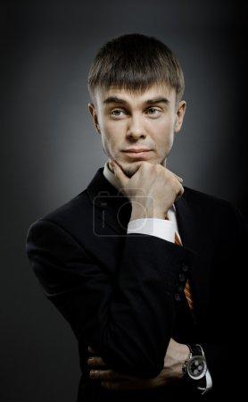 Photo pour Portrait vertical le jeune homme d'affaires en costume, regard fixe, sur fond bleu foncé - image libre de droit