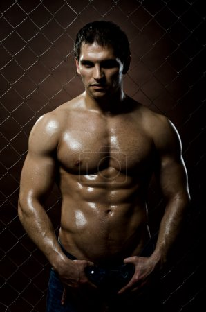Photo for The very muscular handsome sexy guy on dark brown background, strict look - Royalty Free Image