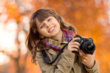 Photo for Horizontal photo, happy beautiful little girl with photocamera, autumnal portrait - Royalty Free Image
