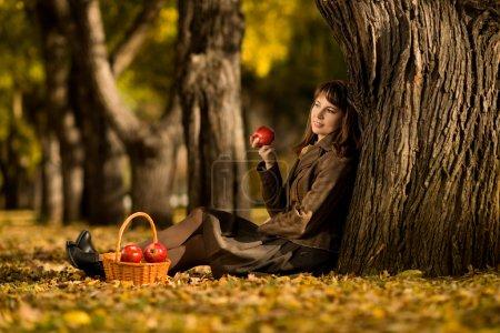 Photo pour Le bonheur mature belle femme assise sur la feuille d'automne et manger de la pomme, en plein air dans le parc - image libre de droit