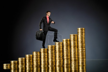 Businessman stand on top of many rouleau gold mone...