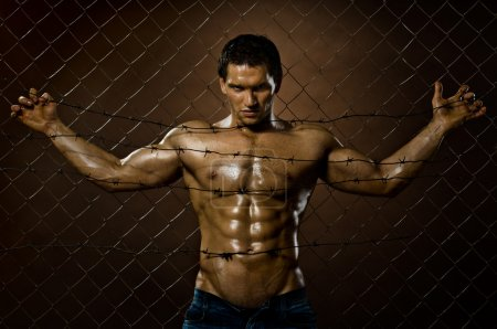 Photo for The very muscular handsome felon guy , misery out of netting steel fence with barbed wire - Royalty Free Image