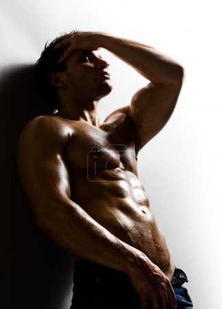 Photo for The very muscular handsome sexy guy on grey wall background - Royalty Free Image