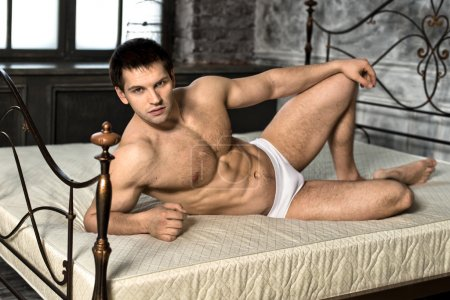 Photo for The very muscular handsome sexy guy lie on bed in bedroom - Royalty Free Image