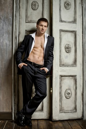 Photo for The very muscular handsome sexy guy in black suit indoor - Royalty Free Image