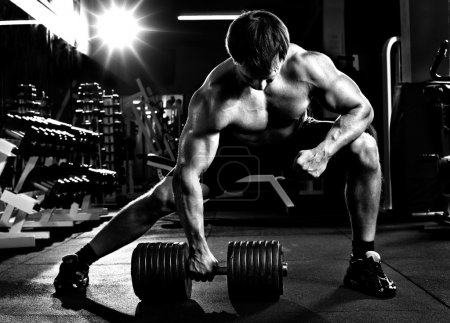 Photo for Very power athletic guy , execute traction with dumbbells, exercise on broadest muscle of back, in sport hall, black-and-white photo - Royalty Free Image