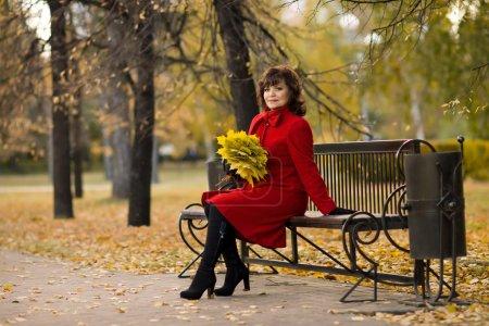 Photo pour La belle femme mature en manteau rouge, en plein air dans le parc, jour d'automne - image libre de droit