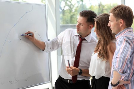 Photo for Business looking at their leader while he explaining something on whiteboard - Royalty Free Image