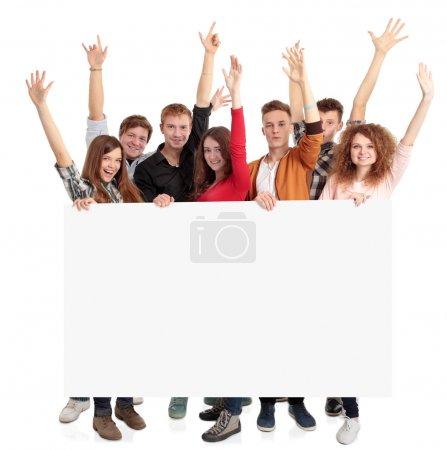 Photo pour Groupe d'amis souriants tenant une bannière vierge - image libre de droit