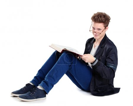 Young man sitting on floor and reading a book, isolated on white background