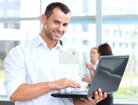 Photo pour Portrait d'un homme d'affaires intelligent à l'aide de portable avec des collègues en arrière-plan - image libre de droit
