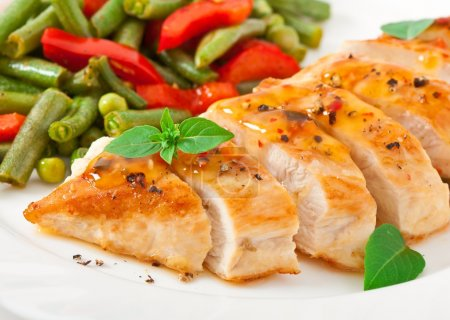 Photo for Chicken breast with vegetables and sauce decorated with basil leaves - Royalty Free Image