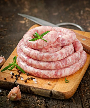 Fresh raw sausage on the old wooden background