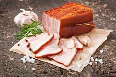 Photo pour Tranches de bacon fumé sur le vieux fond en bois - image libre de droit