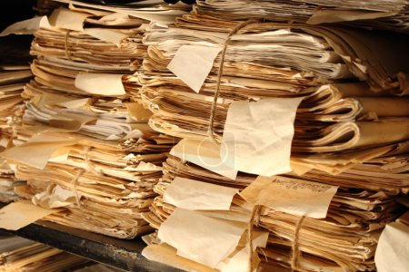 Paper documents stacked in archive...