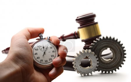 Steel cogwheels, wooden gavel and stopwatch in hand