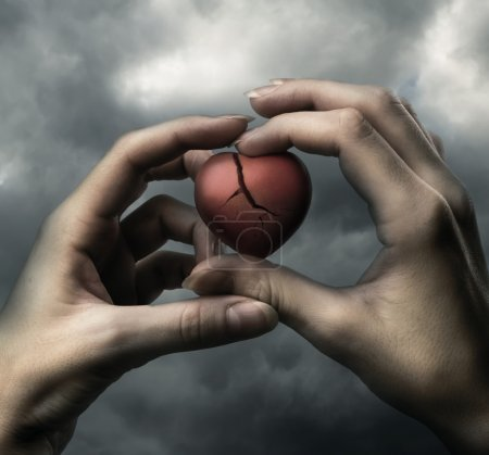 Photo for Broken red heart in hands on stormy sky - Royalty Free Image