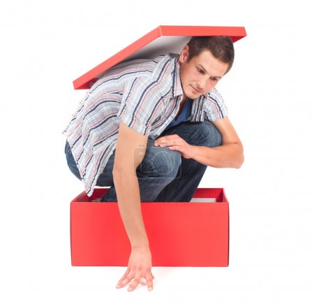 Photo for Young man in a box, seems stuck in his thoughts. - Royalty Free Image