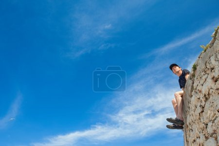 Young man sitting on the edge of wall