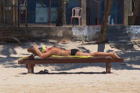 Elderly man sunbathing on wooden bench