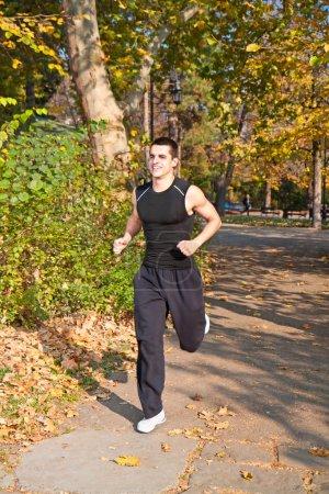 Foto de Joven corriendo en un hermoso parque de otoño - Imagen libre de derechos