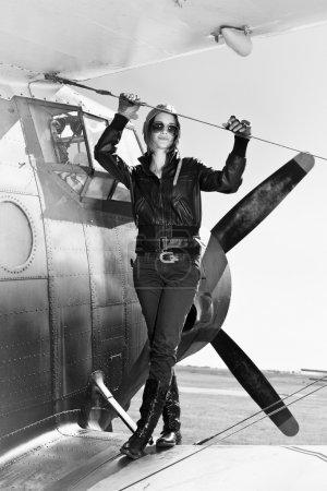 belle fille en due forme veste noire sur un avion de guerre