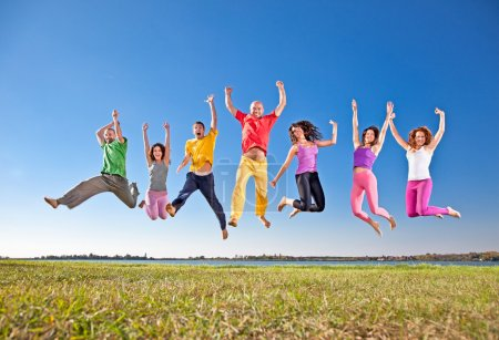 Photo for Happy smiling group of jumping on banch of lake - Royalty Free Image