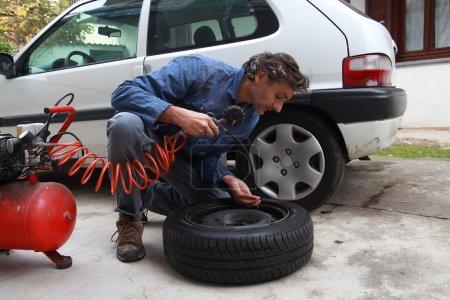 Photo pour Mécanicien caucasien inspectant la pression des pneus - image libre de droit