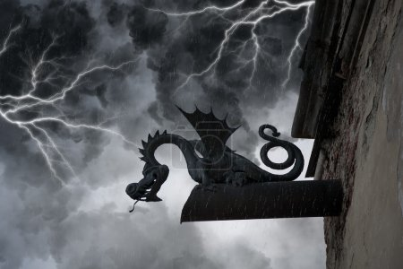 Frightening chimera on the facade of the old castle under thunderclouds and lightning