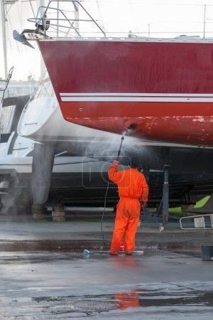 Man cleans a sailboat